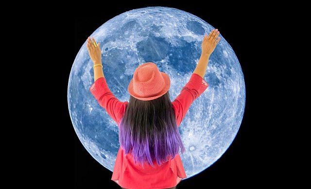 月と手を広げる人